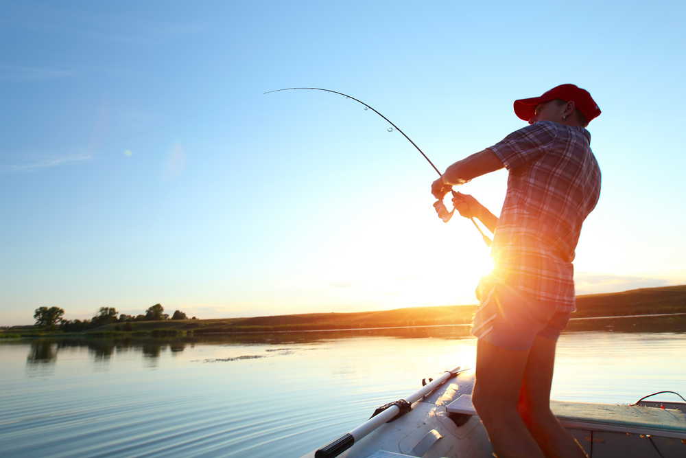 man fishing on his boat with insurance during sunset