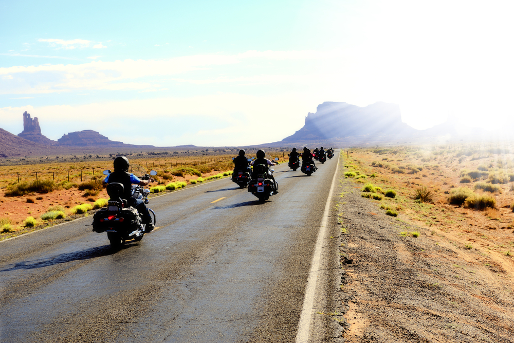 Motorbikers traveling in Monument Valley arizona with helmets on motorcycle
