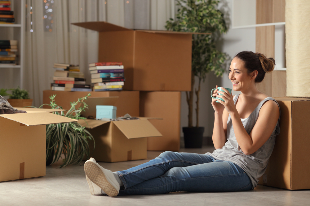 happy young woman sitting in her apartment with renters insurance