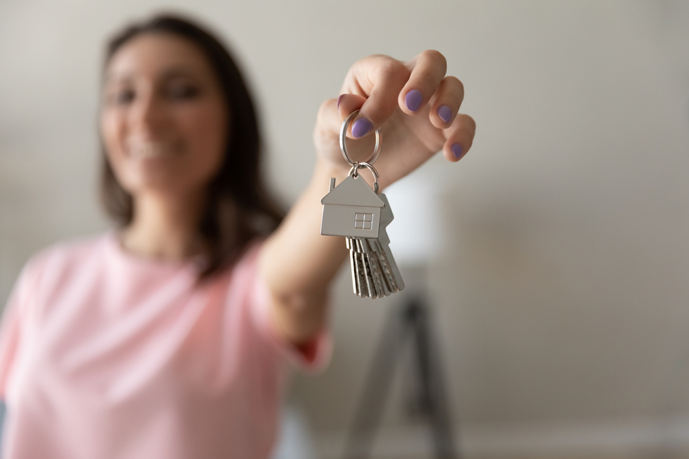 happy woman holding keys to first time rental in arizona