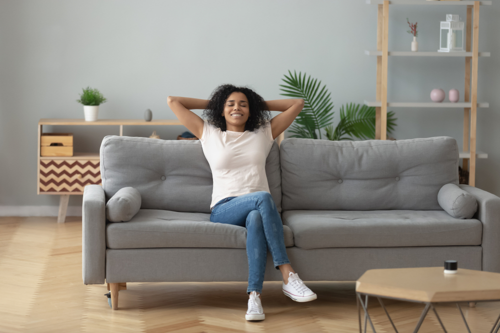 Happy african American young woman in her first-time rental apartments couch