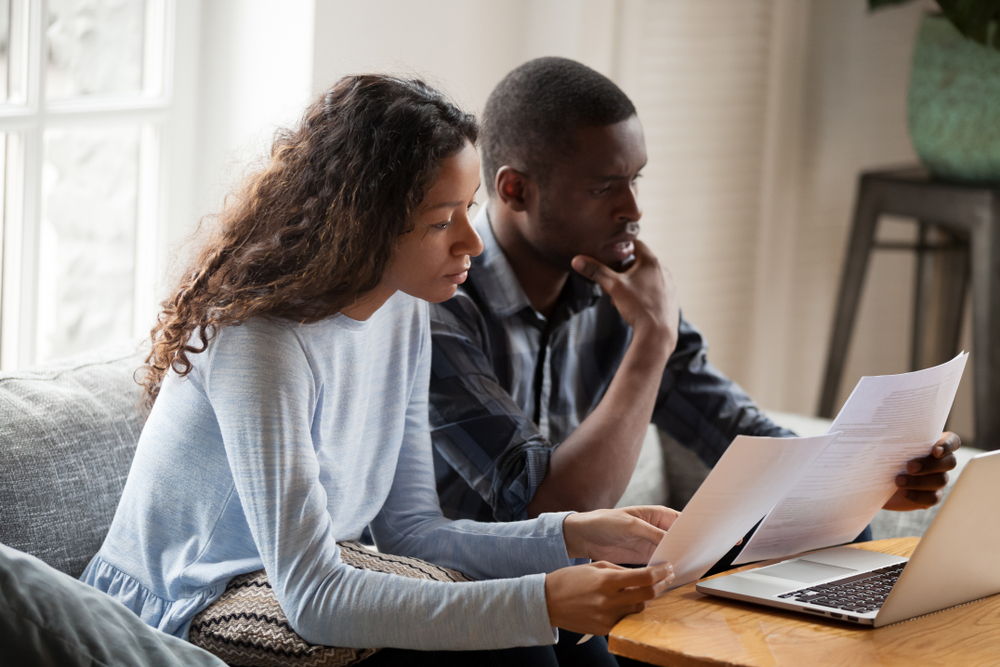 couple looking at renters insurance options on laptop
