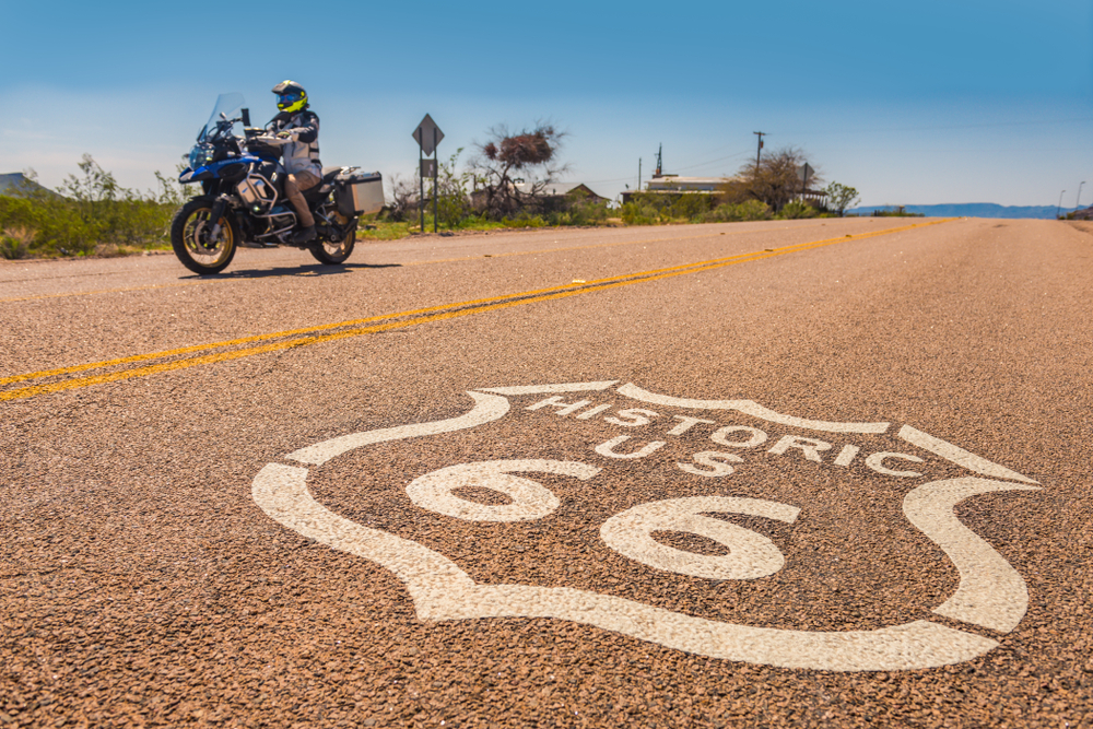 road with a route 66 sign drawn on it with a motorcycle in the background