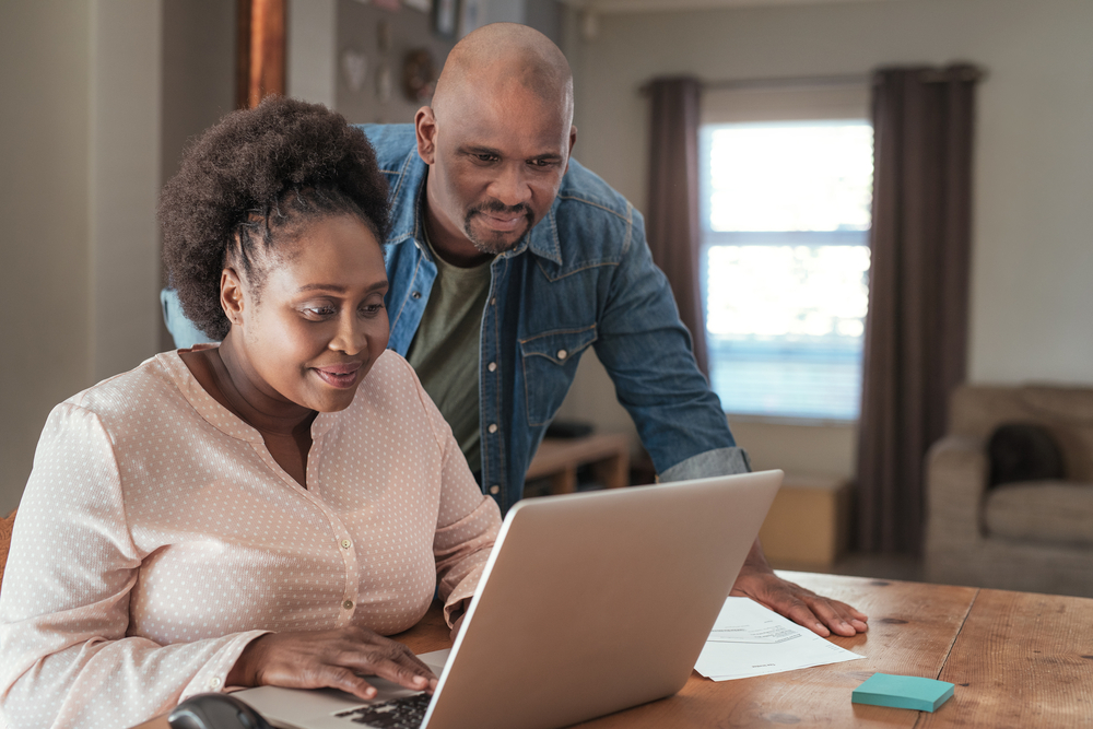 happy african american couple looking for motorcycle insurance in a laptop