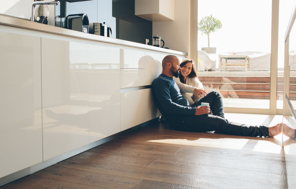 Young man and woman sitting on floor in kitchen and talking