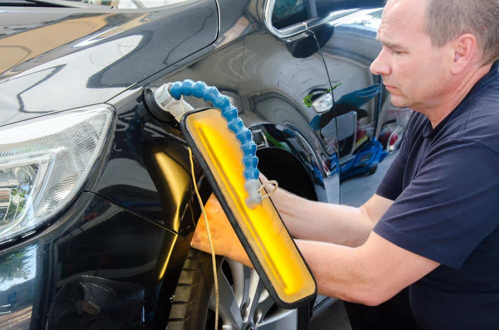 Technician in car service with tools for repairing dents in car body